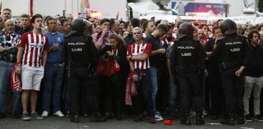 Aficionados del Atlético de Madrid ante agentes de Policía en el exterior del estadio Vicente Calderón.