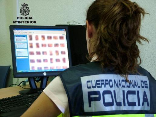 IBIZA - Los jóvenes ibicencos acceden a su primer teléfono móvil y a Facebook con nueve años. EN LA IMAGEN UNA POLICIA NACIONAL MIRANDO UNA PAGINA DE PEDOFILIA.