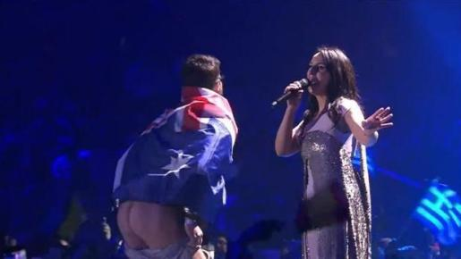 El hombre se subió a gatas al escenario envuelto en una bandera australiana y tuvo tiempo de darse la vuelta, bajarse los pantalones y enseñar alegremente el trasero durante unos instantes sin que los servicios de seguridad ucranianos pudieron evitarlo.