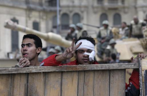 Un manifestante herido levanta una barricada en la plaza Tahrir (de la Liberación), en El Cairo, Egipto, hoy jueves 3 de febrero de 2011.Al menos cinco personas murieron hoy en el centro de El Cairo y otras quince resultaron heridas por disparos hechos por desconocidos contra militantes de la oposición poco antes del amanecer.