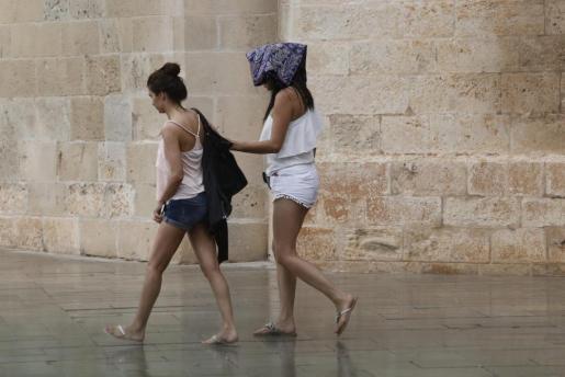 Dos jóvenes pasean por Palma bajo una ligera lluvia.