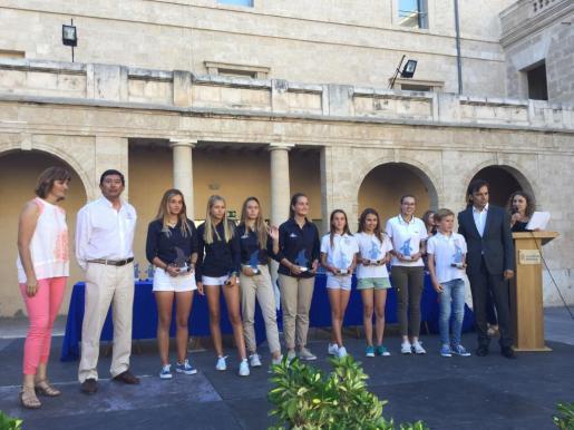 El vicepresident primer, Francesc Miralles, la directora insular d'Esports, Margalida Portells con los deportistas galardonados de la federación de vela.