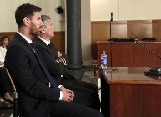 Fotografía de archivo del jugador del FC Barcelona Lionel Messi y su padre, Jorge Horacio Messi (d), en la sala de la Audiencia de Barcelona.
