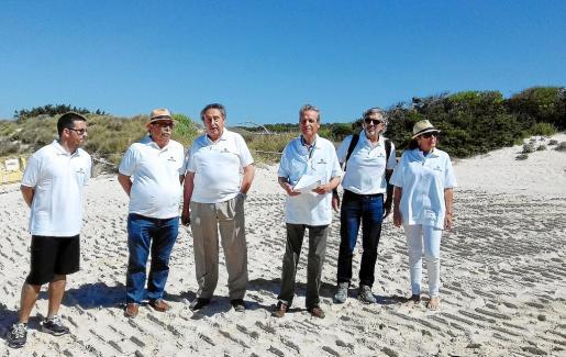 Miembros de Fomento del Turismo escenificaron en ses Covetes su preocupación por «la dejadez» en la playa.