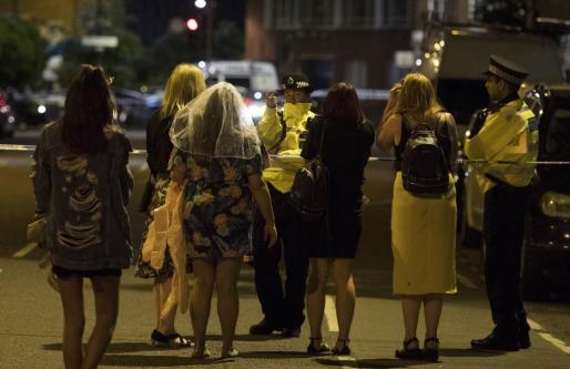 Agentes de policía tratan con un grupo de afectados por el atentado de este sábado en Londres.