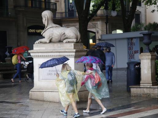 La lluvia sorprendió a los turistas, que incluso recurrieron al chubasquero.