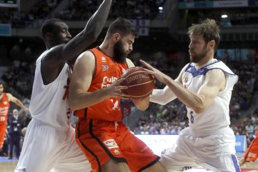 Los jugadores del Real Madrid Andrés Nocioni (d) y Othello hunter (i) intentan arrebatar el balón al pívot del Valencia Basket Bojan Dubljevic.