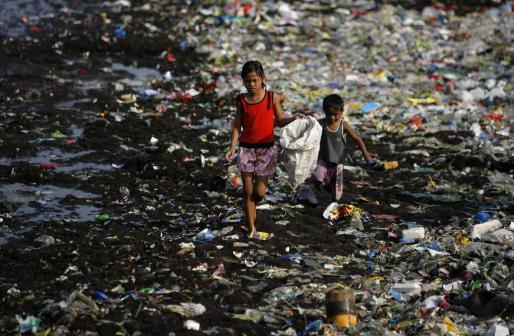 Imagen de niños filipinos trabajando recogiendo materiales útiles en la línea de costa de los suburbios de Manila.