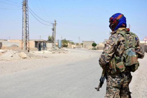 Soldados vigilan una carretera durante los enfrentamientos entre el Estado Islámico (EI) y las Fuerzas de Siria Democrática (FSD) en Al Raqa.