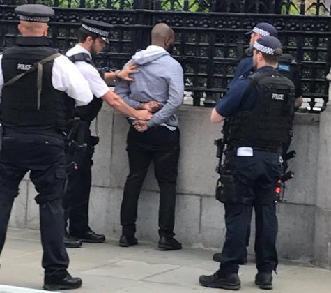 Imagen de varios agentes con el hombre arrestado en los alrededores del Palacio de Westminster.