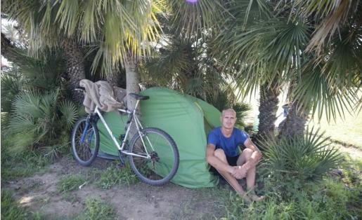 Ramikaitis con su tienda y su 'bici' entre las palmeras.