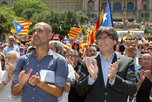 El presidente de la Generalitat, Carles Puigdemont (derecha), y el exentrenador del FC Barcelona Pep Guardiola en un acto de apoyo al referéndum en Cataluña.
