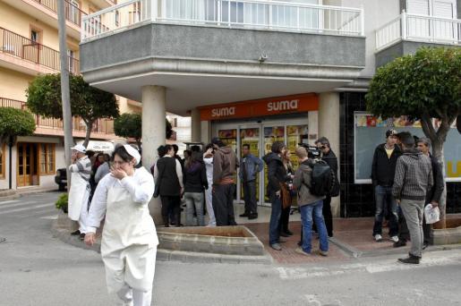 Varias personas a las puertas del supermercado y junto a varias de las calles del centro del municipio de Sant Antoni, en Ibiza, donde hoy un ciudadano marroquí de 41 años ha apuñalado indiscriminadamente a una decena de personas.