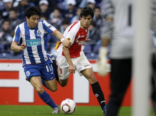 El jugador del Oporto, Fucile Perdomo (izq.) lucha por el balón con el jugador del Sevilla Diego Perotti.