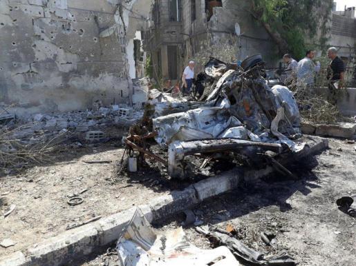 Varias personas ispeccionan los restos de uno de los coches bomba que han causado varios muertos en Damasco.
