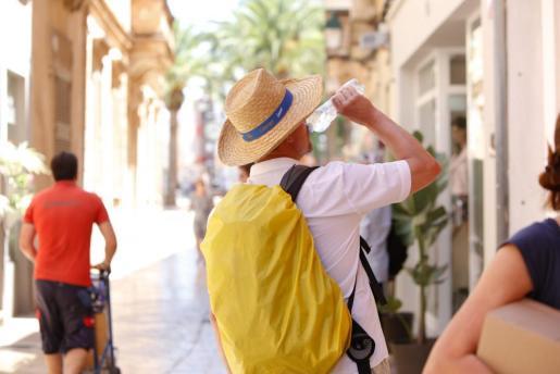 Un turista hidratándose a causa de la calor en Ciutadella.