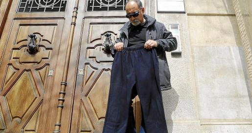 Juan Albertí, hijo de la mujer que sufrió quemadaduras, muestra los pantalones que compró ella por ocho euros en Pere Garau.