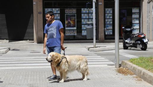 Kini, vendedor de la ONCE, junto a 'Jaguar' en el paso de peatones donde ocurrieron los hechos.