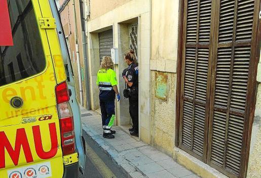 Una agente de policía y personal del 061, en el portal de la finca de la víctima.