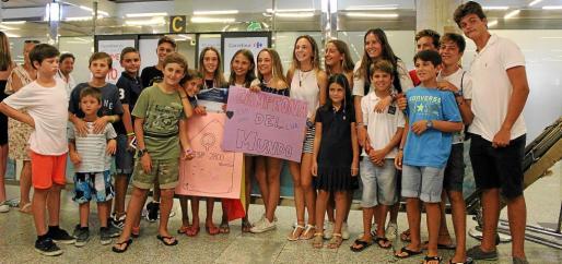 María Perelló posa junto a los jóvenes regatistas del Club Nàutic s'Arenal y amigos que acudieron este sábado a la terminal del aeropuerto de Son Sant Joan para recibirla tras proclamarse campeona del mundo de la clase Optimist en aguas de Pattaya (Tailandia).