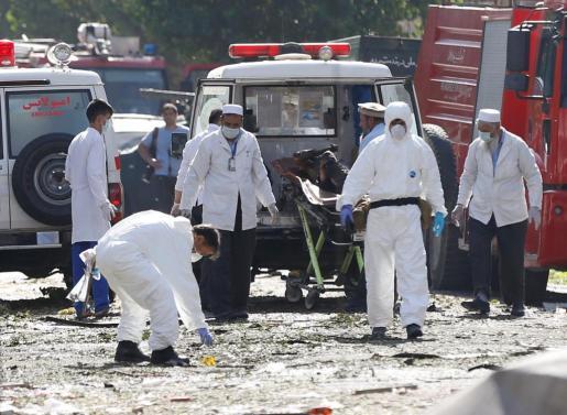 Personal sanitario e investigadores examinan el lugar del atentado atendiendo a las víctimas del atentando terrorista que ha sacudido Kabul la mañana de este lunes y que ha costado la vida de al menos 24 personas.