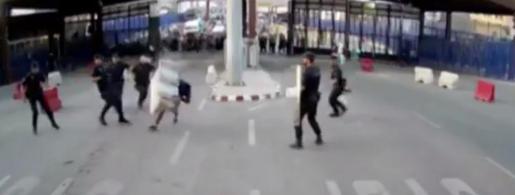 Instante en el que el hombre es reducido por la policía tras arrojarle una valla de plástico.