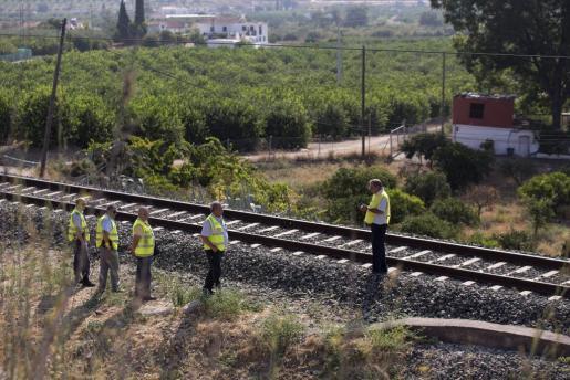 Técnicos de ADIF inspeccionan la zona acotada de la vía férrea donde un maquinista de un tren de Cercanías detuvo el ferrocarril a primera hora de la mañana al percatarse de que había un cuerpo de una niña junto a la vía.