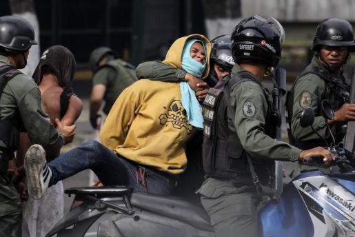 La Guardia Nacional Bolivariana (GNB) aprehende a un manifestante durante enfrentamientos contra opositores este jueves Caracas.