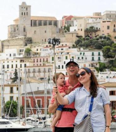 Una familia se hace un selfie en el puerto de Eivissa con Dalt Vila y la catedral de fondo.
