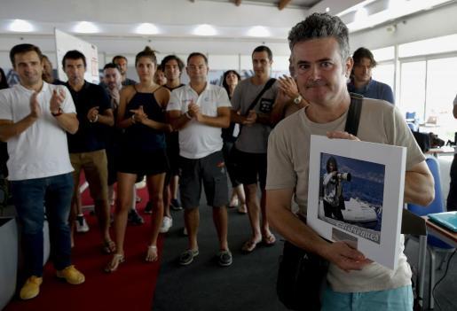 Alonso Gamero (d), pareja de la fotógrafa de la Agencia Efe Montse Diez, muestra una fotografía con la imagen de Montse sosteniendo la cámara de fotos durante la cobertura de una de las regatas.