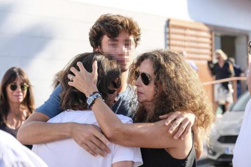 Belinda Alonso (d), mujer de Ángel Nieto, se abraza a Gelete (i) y Hugo (c), al cierre del velatorio del expiloto.
