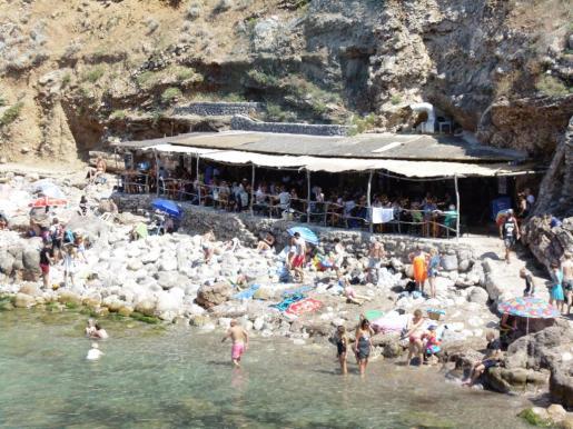 El chiringuito se halla a pie de playa, entre las rocas y el acantilado.