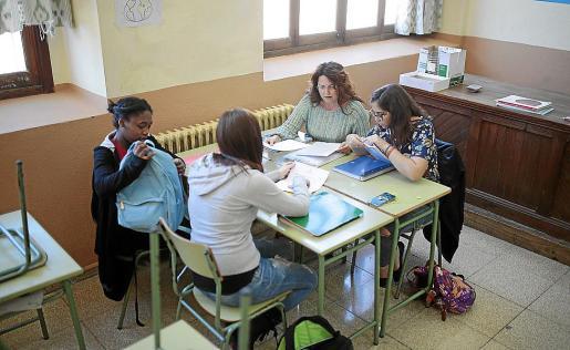 Una profesora de Secundaria, reunida con tres alumnas en un aula.