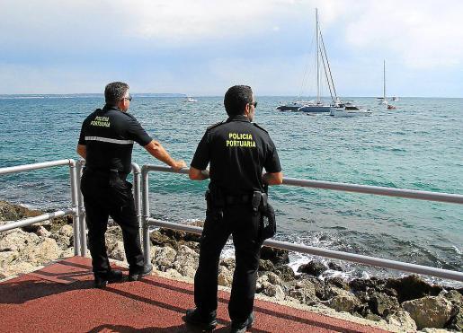 Dos agentes de la Policía Portuària observan las maniobras desde primera línea.