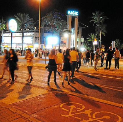 En la imagen, cientos de jóvenes transitando las calles de Alcudia con el propósito de salir de fiesta. En el lateral, un miembro de la Policía Local del municipio controlando la escena.