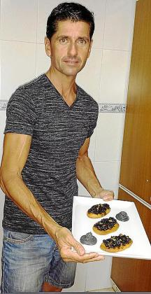 Pedro Antonio Colom posa con sus mini cocas de sepia con cebolla confitada en su tinta con piñones con alioli negro.