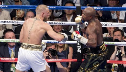 El luchador de artes marciales mixtas, el irlandés Conor McGregor (i), en acción ante el boxeador estadounidense Floyd Mayweather (d).