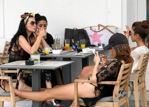 Un grupo de turistas se relaja en una terraza del puerto de Eivissa.