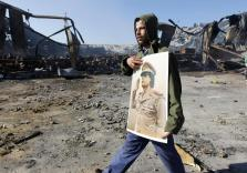 A Libyan holds a poster of Libya's leader Muammar Gaddafi as he walks past a naval military facility damaged by coalition air st