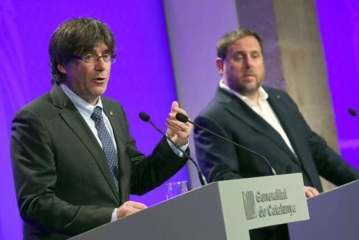 El presidente de la Generalitat, Carles Puigdemont, y el vicepresidente del Govern y conseller de Economía, Oriol Junqueras comparecen ante los medios de comunicación en el Palau de la Generalitat.