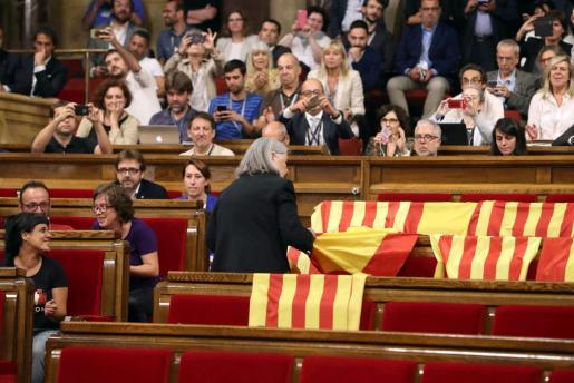 La diputada de la coalición en la que está integrada Podemos, Àngels Martínez, retira las banderas de España de los escaños del PPC después de que los diputados de Ciudadanos, PSC y PPC abandonasen sus escaños en el Parlament para no votar la ley del referéndum.