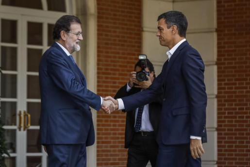 El presidente del Gobierno, Mariano Rajoy, saluda al secretario general del PSOE, Pedro Sánchez, en el Palacio de la Moncloa.