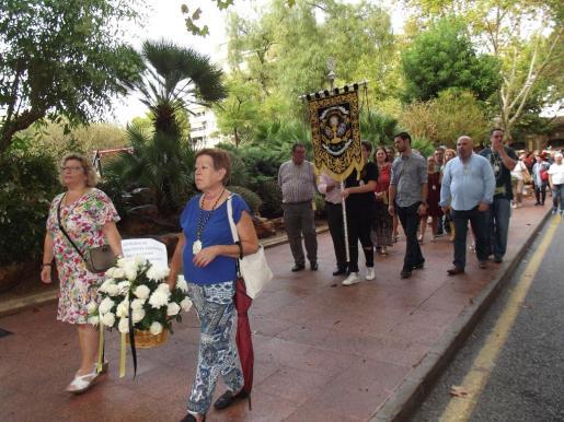 El desfile, a su salida de la plaza Berenguer de Palou, con dos mujeres integrantes de una cofradía portando flores.