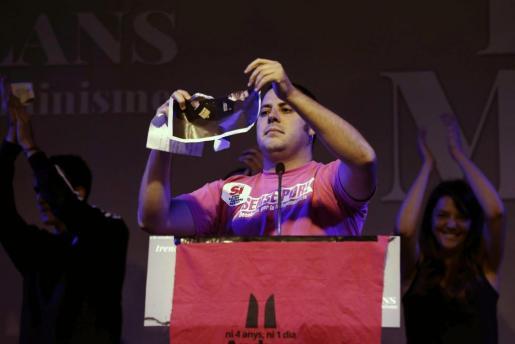 Un independentista rompe la foto del Rey durante el acto que la CUP ha celebrado esta tarde en el centro de Barcelona con motivo de la Diada.