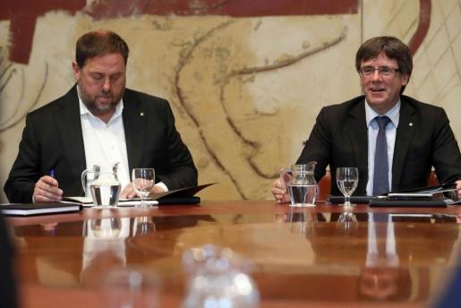 El presidente de la Generalitat, Carles Puigdemont (d), junto al vicepresidente, Oriol Junqueras (i), durante la reunión semanal del Govern, la primera después de la firma del decreto de convocatoria del referéndum sobre la independencia de Cataluña para el 1 de octubre, suspendido por el Tribunal Constitucional, y tras la manifestación de la Diada.