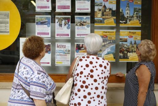 Pensionistas, mirando los carteles de los viajes del Imserso.