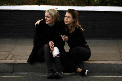 Dos chicas, sentadas en la acera tras la explosión.