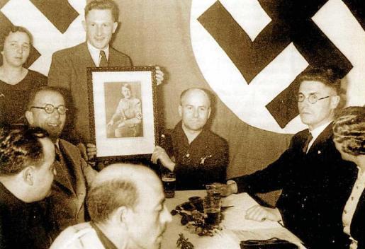 De pie y sosteniendo un retrato del fürer aparece Walter Rup, jefe del partido en Mallorca. Le ayuda a sostenerlo, sentado, elmarqués Alfonso de Zayas y de Bobadilla, jefe de la Falange en la Isla y uno de los promotores de la terrible represión tras el inicio de la Guerra Civil. También está el cónsul Hans Dede.