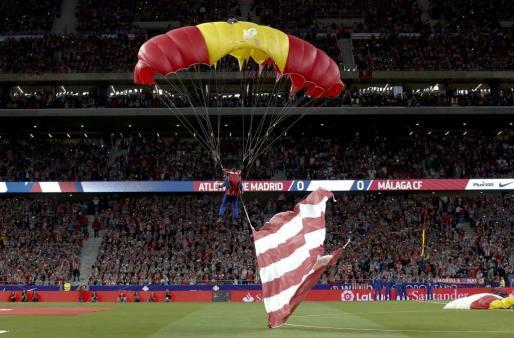 Un paracaidista con una bandera rojiblanca aterriza en el estadio Wanda antes del partido entre Atlético de Madrid y Málaga.