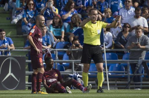 El delantero francés del Barcelona Ousmane Dembélé (c) se lesiona durante el partido ante el Getafe.